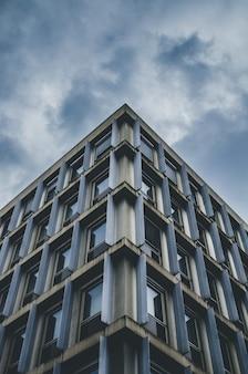Tiro de ângulo baixo vertical de um prédio azul e cinza sob um céu nublado