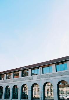 Tiro de ângulo baixo vertical de um prédio de concreto com janelas reflexivas sob o céu claro