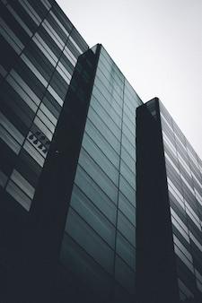 Tiro de ângulo baixo vertical de um prédio preto com janelas de espelho sob o céu claro