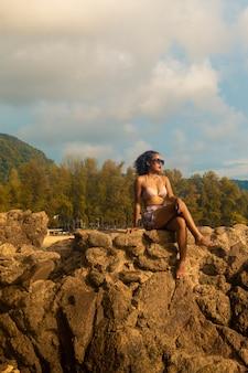 Tiro de ângulo baixo vertical de uma mulher sentada em uma formação rochosa, aproveitando o dia bonito