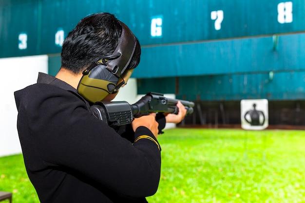 Tiro de arma por duas mãos no campo de tiro da academia.