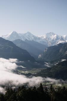 Tiro de bela paisagem vertical de montanhas e colinas, rodeado por árvores sob um céu claro