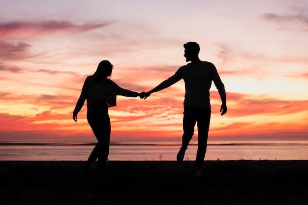 Tiro de casal de mãos dadas ao pôr do sol