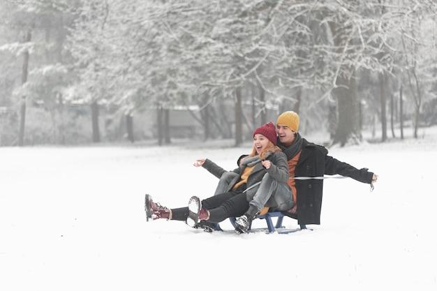 Tiro de casal sendo feliz e sentado no trenó