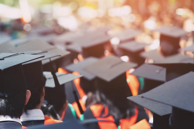 Tiro de chapéus de formatura durante os graduados de sucesso de formatura da universidade. cerimônia de graduação.
