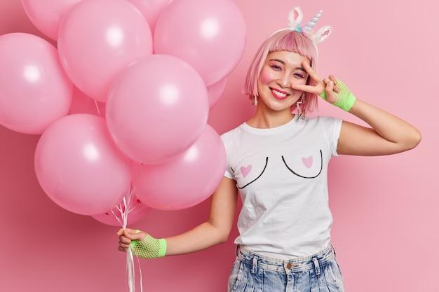 Tiro de cintura para cima de mulher de cabelo rosa asiática faz gesto de paz sobre sorrisos de olhos agradavelmente vestido com jeans e camiseta casual se diverte na festa. conceito de entretenimento e celebração de alegria de pessoas