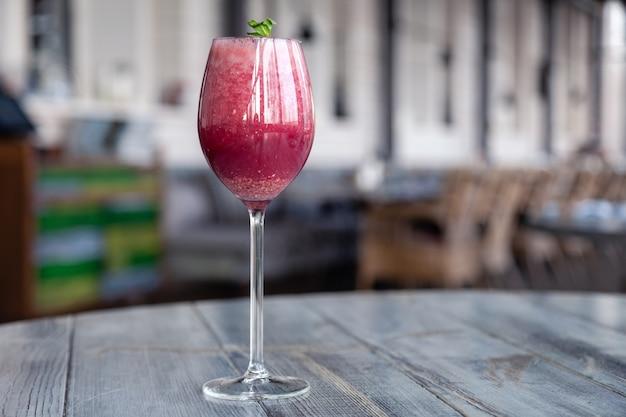 Tiro de comida. berry cocktail em copo de cristal decorado hortelã, frutas, romã, laranja, abacaxi.