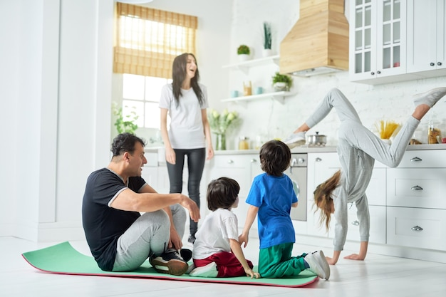 Tiro de comprimento total de família latina feliz tendo treino matinal juntos em casa. família, conceito de esporte