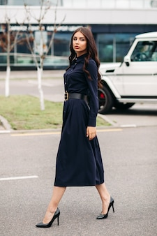 Tiro de comprimento total de jovem linda elegante com vestido preto e andando na rua da cidade. estilo e conceito de moda