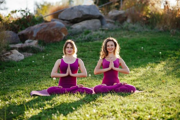 Tiro de comprimento total de uma mulher bonita saudável feliz meditando na posição de lótus ao ar livre. mulher bonita, relaxante, meditando no parque, sentado na grama
