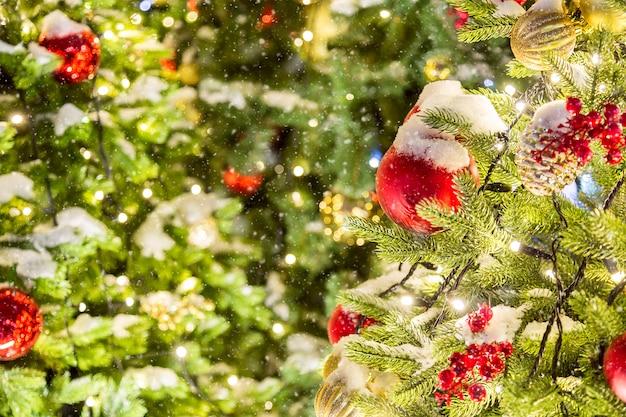 Tiro de detalhe de galhos de árvores de natal com brinquedos de natal, luzes e neve
