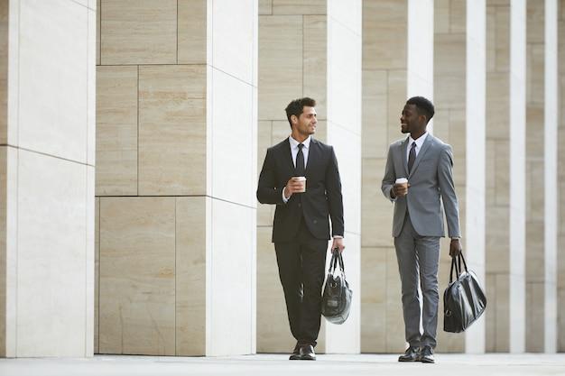 Tiro de dois empresários passeando pela cidade com copos de café para viagem