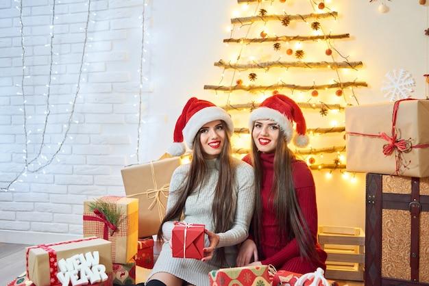 Tiro de duas irmãs gêmeas feliz sentado em casa, rodeado de natal