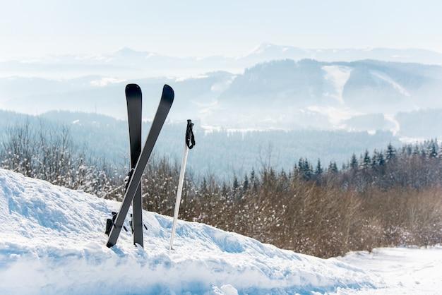 Tiro de esquis na neve no topo de uma montanha