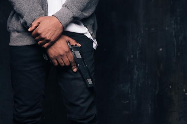 Tiro de estúdio de homem negro criminoso armado irreconhecível