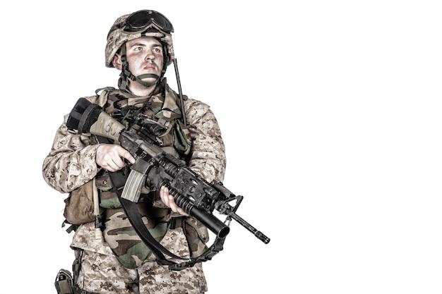 Tiro de estúdio de infantaria marinha, soldado de comando com munição de proteção completa, em pé com o lançador de granadas equipado com rifle de serviço e olhando para a câmera, isolado no fundo branco