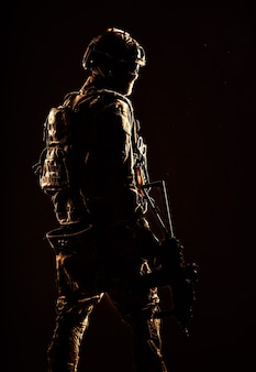 Tiro de estúdio discreto de soldado das forças especiais do exército, lutador de comando com máscara, óculos balísticos, capacete tático e uniforme de batalha, segurando rifle de serviço de cano curto, olhando para trás por cima do ombro