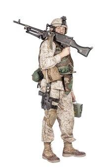 Tiro de estúdio do exército, fuzileiro naval em uniforme de combate de camuflagem e armadura corporal, em pé com a metralhadora no ombro, segurando a caixa de munição na mão e olhando para a câmera, isolado no branco