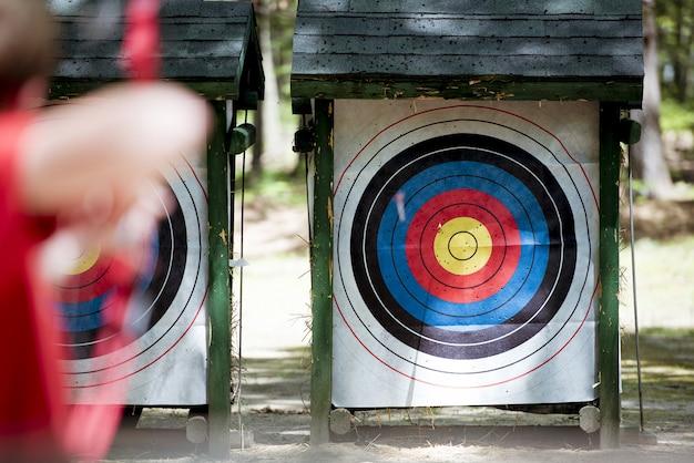Tiro de foco seletivo de um alvo com uma pessoa borrada usando arco e flecha