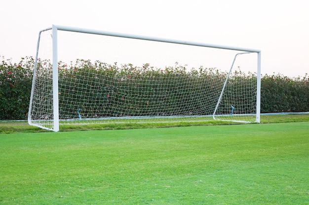 Tiro de gol de canto na frente, campo de futebol, balizas e redes vazias de futebol amador