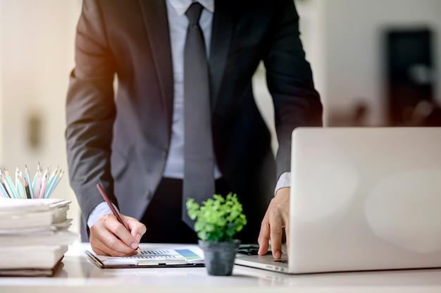 Tiro de homem de negócios, trabalhando com laptop e papelada no escritório