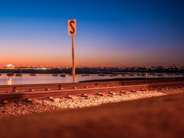 Tiro de longa exposição da ferrovia de faros no pôr do sol e no mar.