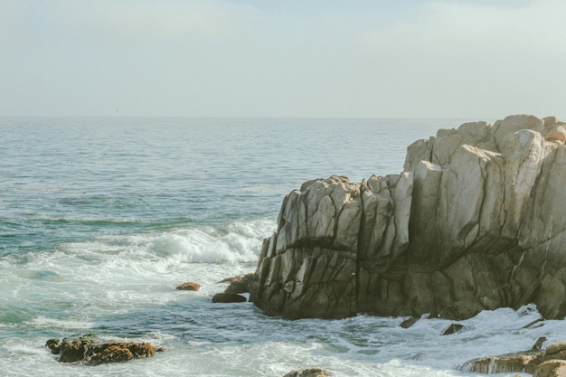 Tiro de longo alcance das ondas do mar atingindo o penhasco