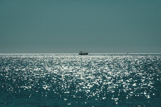 Tiro de longo alcance de um barco navegando no mar, refletindo o sol