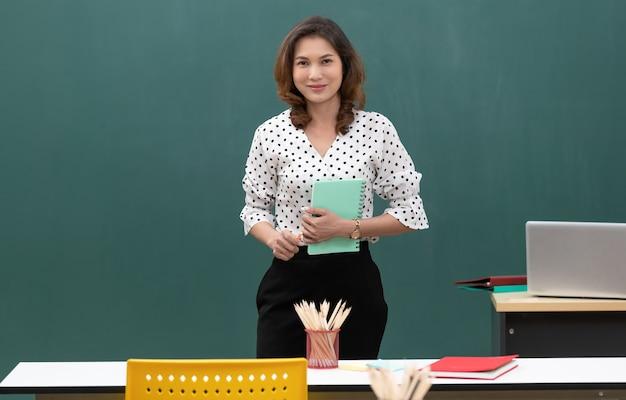 Tiro de luz de flash de estúdio, linda mulher asiática segurando o livro e giz em pé na frente do quadro negro com espaço de cópia.