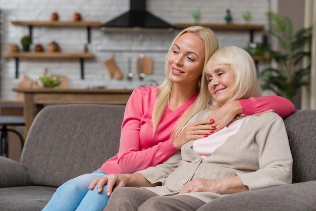 Tiro de mãe e filha sentada em um sofá