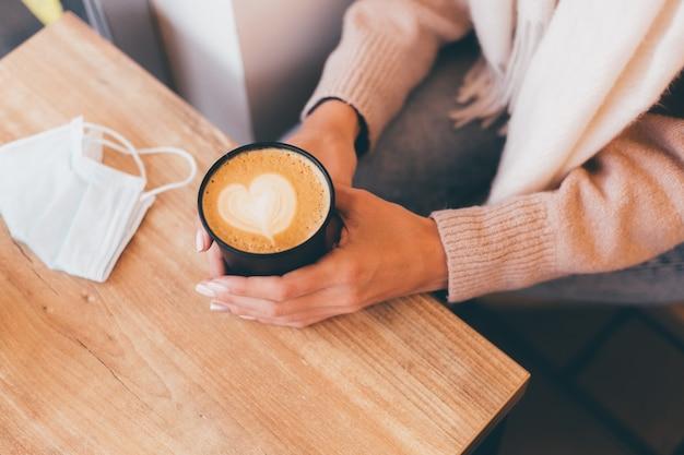 Tiro de mãos de mulher segure uma xícara de café quente com desenho de coração feito de espuma.