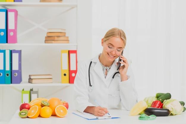 Tiro de médio sorridente nutricionista falando ao telefone