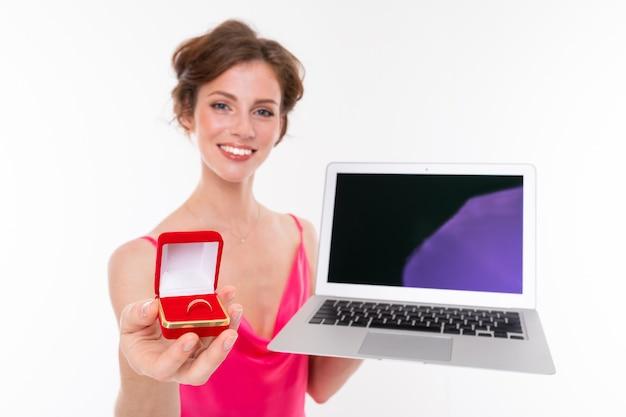 Tiro de meio comprimento da noiva com anel de noivado e laptop