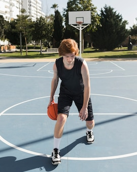 Tiro de menino jogando basquete