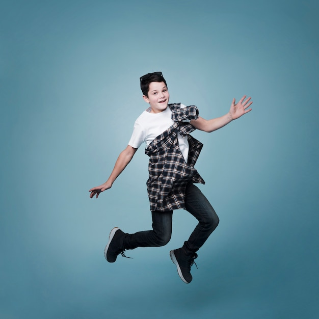 Tiro de menino pulando e posando