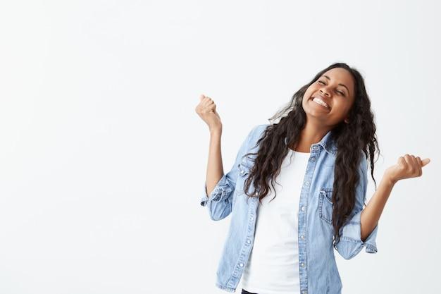 Tiro de mulher bem sucedida de pele escura, com longos cabelos ondulados, vestindo camisa jeans apertando os punhos de emoção, sendo feliz em comemorar sua conquista e sucesso.