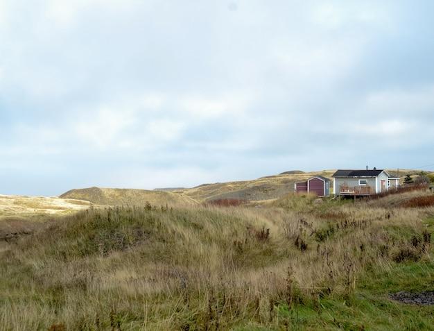 Tiro de paisagem de um campo de grama seca com uma casa visível à distância