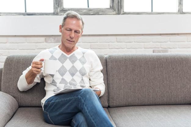 Tiro de tiro médio homem lendo no sofá
