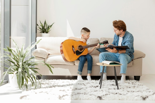 Tiro de tutor e menino tocando violão
