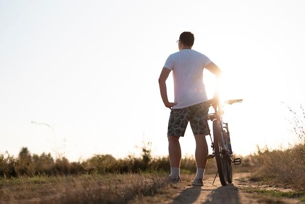 Tiro de um homem com uma bicicleta, olhando para longe