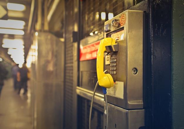 Tiro de um telefone público amarelo e cinza