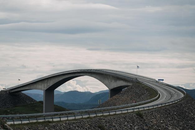 Tiro de uma estrada longa viaduto perto de montanhas sob o céu