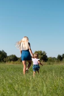 Tiro de uma mulher e uma menina andando