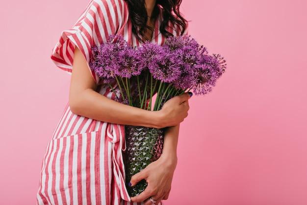 Tiro de violetas flores silvestres em vaso closeup. menina com vestido rosa contém buquê.