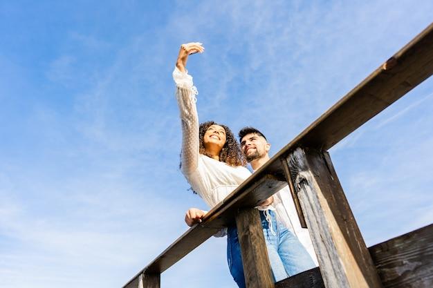 Tiro de visão incomum de baixo ângulo de casal multirracial em uma ponte de madeira da praia, tomando uma selfie em férias no mar oceano resort. grande espaço de cópia do céu ideal para banners ou anúncios. garota hispânica usando smartphone