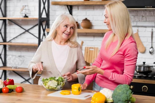 Tiro de vista frontal de mãe e filha conversando na cozinha