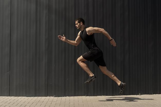 Tiro de vista lateral de um homem jovem e atlético apto pulando e correndo.