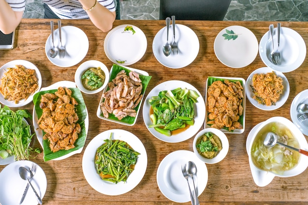 Tiro de vista superior; alimentos locais tailandeses dispostos na mesa de madeira, e uma mulher asiática estava esperando e pronta para comer.