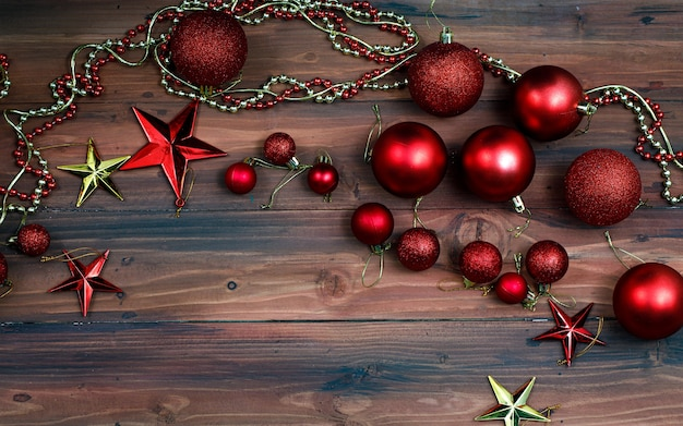 Tiro de vista superior do festival de natal e itens decorativos de feliz ano novo. bolas vermelhas brilhantes de decoração, corrente de pérola de lâmpada de prata e estrela dourada brilhante colocada na velha mesa de madeira escura com espaço de cópia.