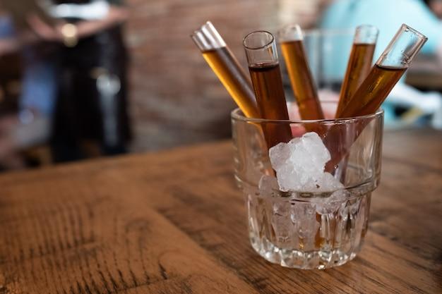 Tiro de vodka de doces em tubo de vidro dentro de vidro com gelo